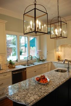 This 1920's colonial home in Clayton, NC was a fun and wonderfully challenging remodel. We were able to bring this kitchen up to date while conserving the integrity of the house. Every feature and every little detail in this kitchen says Wow.  It features simple off white cabinets with a black island, Cambria quartz countertops, stainless steel appliances, off white subway tile with gray grout, and beautiful birdcage pendant lights.  Photo credit: Rima Nasser