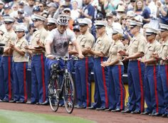 Doug Jones, a wounded Marine veteran, rides a bike past fellow Marines as he enters Petco Park in San Diego to throw out the ceremonial first pitch before the Detroit Tigers-San Diego Padres game