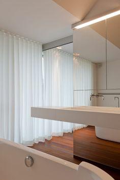 witte lange gordijnen voor het groot raam in de badkamer en logee