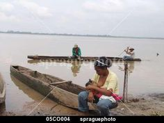 Woman breast feeding her baby beside the Rio Magdalena, Barrancabermeja. Fishermen go passed in a dug out canoe, Colombia.
