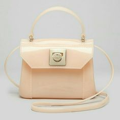 Furla Mini Candy Crossover Bag A petite Furla handbag in shiny, translucent rubber. Short handle and optional shoulder strap. Hinged closure and unlined interior. BRAND NEW WITH TAG. Peach color.   Fabric: PVC Weight: 12oz Made in Italy.  Measurements Height: 4.75in / 12cm Length: 6.25in / 16cm Depth: 2.75in / 7cm Strap drop: 22.5in / 57cm Handle drop: 2.75in / 7cm Furla Bags Crossbody Bags