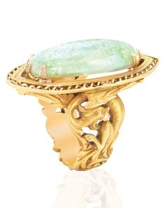 Art Nouveau Gold and Opal Ring. Centring one oval opal approximately 22.0 x 9.3 x 5.6 mm., within finely ribbed and filigree gold, the shank fashioned of a stylised scrolled leaf motif, circa 1900.