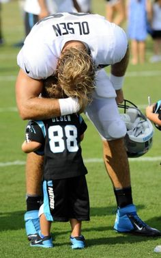 Carolina Panthers tight end Greg Olsen greets his son, Tate, afternoon practice on Tuesday, Aug. 5, 2014, during training camp at Wofford College in Spartanburg, S.C. (David T. Foster, III/ Charlotte Observer/MCT)