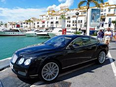 A Bentley cruises the oceanfront at Marbella Beach, Playa Andulusia, Spain