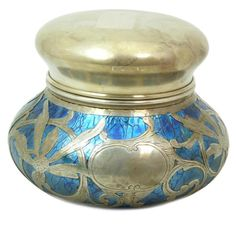 """Loetz blue iridescent art glass round covered box having a scrolled floral sterling silver overlay design. Marked 'STERLING' to cover and rim. Measures approx. 3 3/4"""" height x 4 3/4"""" diameter. Total weight approx. 313 grams."""