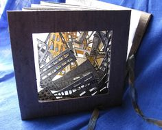 Tunnel Book by Pauline A. Braun, Winnipeg, Manitoba, Canada. The intaglio prints within the book are pulled from two etched copper plates. The front and back boards are covered with paste paper. The accordion folded side panels are vellum. The book measures 15 x 15 x 45 cm (extended).
