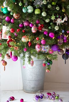 A small Christmas tree covered in bright ornaments - and placed in a galvanized French bucket.