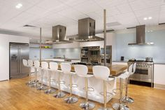 White matte leather barstools continue the color scheme of the room with grain light wood countertop. The large kitchen island with seating and storage offers plenty of space for cooking prep and double as a breakfast bar