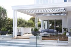 A new outdoor living area featuring overhead louvres and heaters is a key part of the extensive bungalow renovation by . Porches, Outdoor Living Areas, Outdoor Rooms, Bungalow Renovation, Alfresco Area, Hamptons House, Pergola Designs, Pergola Ideas, Pergola Shade