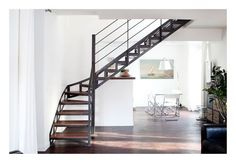 Un escalier quart tournant au look industriel par Escaliers Décors. Photo : Nicolas Grandmaison. Cet escalier rappelle l'âge d'or des constructions en acier de la fin du 19ème siècle. Les limons structurés apportent du caractère et de la présence à l'escalier tout en légèreté. Escalier Esca'Droit® quart tournant intermédiaire. Escaliers Décors.