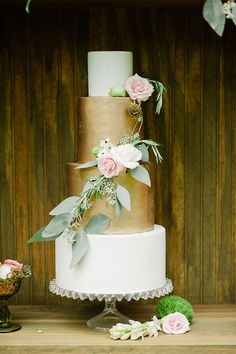 Gilded wedding cake adorned with a cascade of roses and greenery | Photo by Merari Photography