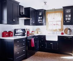 Sleek Cottage Style Kitchen with Painted Black Cabinets.  Love the red accessories like that red canisters, utensil holder, and towel.