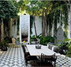 Beautiful black and white tiles with coordinating outdoor dining table and chairs in an ivy-lined courtyard.: