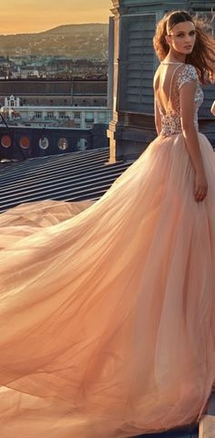 The dramatic GALA-607 is a ballerina ball gown with a full blush organza skirt, cathedral train, and a plunging bodice encrusted in sequins and pearls. The Perfect wedding dress for the bride who looks for a princess bohemian style!