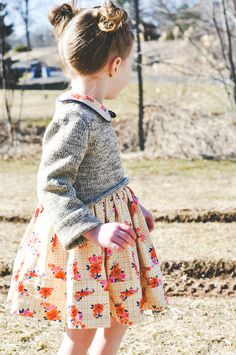 love her little cropped grey sweater, princess Leia hair and floral dress.  #estella #kids #fashion