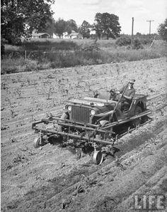 Early CJ2A Willys Jeep plowing in a field.