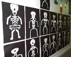 """Look closely: students folded white paper in half, wrote their names in cursive, and cut out around their names - this formed the body. They added the head, arms,and legs then mounted their """"name skeletons"""" on black construction paper!"""