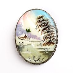 Russian Village in Winter Pin - $52.99 This Winter scene mother-of-pearl pin was painted in Russia and bears the initials of the artist on the front.. It features a magnificently detailed miniature painting of a classic Russian Winter village. It is made of a luminescent mother of pearl base that is nested into a German silver frame with a pin on the back. Each brooch is painted in the classical Fedoskino style. Fedoskino is the famous Russian school of miniature painting.