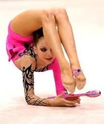 es una mujer que se esta parando sobre sus codos y usando sus pies como manos