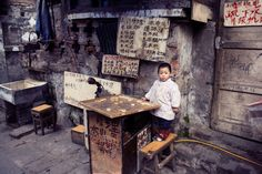"""On the Stairs"". While climbing Chongqing's famous stairs to city centre, this young girl called out to me. She didn't speak any English, but her grandfather tried desperately to get her to say ""Hello"". Location: Chongqing, China. (Photo and caption by Megan Steen/National Geographic Traveler Photo Contest)"