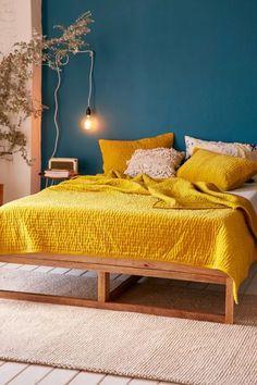 A dupla verde e amarelo ficou sofisticada no décor deste quarto, com o tom petróleo da parede de destaque e o mostarda da roupa de cama.