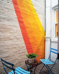 This brick wall mural certainly brightens up an outdoor space that could otherwise be an eyesore. Nice use of color to pop against the dull white wall.
