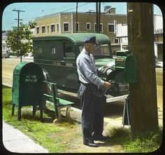 Letter carrier uses his key to unlock a mail collection box mounted to a telephone pole. A postal distribution box (used by mail carriers and clerks to store mail for neighborhood delivery) and a U.S. Mail truck are in the background. Hand-colored photographic print from 1947.
