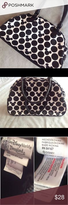 """Hidden Mickey Disney Bowler Handbag Purse Good used condition. Bowler bag style purse by Disney in black-and-white """"hidden Mickey"""" polka dot print. Synthetic, not real leather: easy wipe down to clean. Great bag for a mom on the go (or someone who doesn't want to be too delicate with their bag). Solid black handles, bottom and interior with a slip pocket and zippered pocket inside. Some minor marks & spots throughout bag (see photos), can likely be cleaned. Walt Disney World & Disneyland…"""