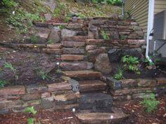 Cet escalier est intéressant à plusieurs niveaux : les paliers permettent de planter plusieurs plantes autour de l'escalier pour redonner vie au lieu. Les pierres taillées sont de diverses couleurs et sont utilisées sur toute la façade pour un maximum de cohérence et de réalisme. Un projet d'aménagement paysager par Maxhorti au Québec. #Landscaping