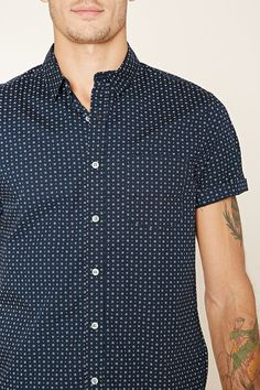This slim fit woven shirt features an allover abstract polka dot print, short sleeves, a basic collar, a buttoned front, a slightly curved hem, and a chest patch pocket.