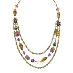 You've never seen a beaded necklace like this before! Resting between two brass tone French rope style chains, a strand of beads adds a wonderful array of colors and textures. The medley includes square marbleized amethyst beads, iridescent purple lantern beads, and baroque shaped smoke topaz beads that are given a bronzed metallic detailing for even more color and shine! So get this eye-catching layered look all in one necklace!