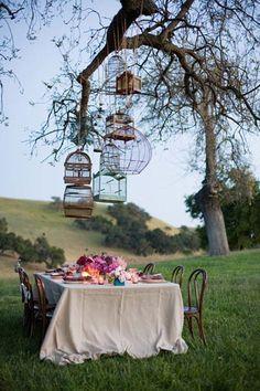 Goed idee voor een tuinfeestje wanneer het eindelijk opnieuw wat beter weer is: Een zee van bloemen op tafel, en een reeks oude vogelkooien erboven. Superromantisch!
