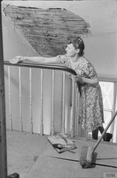 A DAY IN THE LIFE OF A WARTIME HOUSEWIFE: EVERYDAY LIFE IN LONDON, ENGLAND, 1941. Mrs Olive Day spends half an hour or so on the housework before she leaves for work. Here we see her polishing the bannisters. Above her head, we can see a large patch of missing plaster on the ceiling, caused by a nearby air raid.