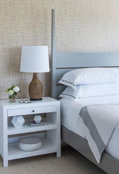 A gray poster bed finished with a plank headboard is dressed in black and white bedding and positioned on a tan sisal rug against a tan sisal wallpapered wall beside a white lacquered nightstand with two shelves lit by a wood lamp.