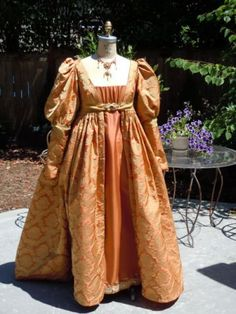 This Italian Renaissance dress is made from a coral and gold colored jacquard. It features the distinctive waist, finishing half way between the bust and natural waistline.
