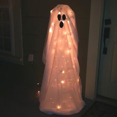 Turn a tomato cage upside down, add Christmas lights, sheet and face!! Adorable Halloween decor idea!