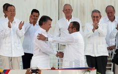 Colombia's President Juan Manuel Santos, front left, and the top commander of the Revolutionary Armed Forces of Colombia (FARC) Rodrigo Londono, known by the alias Timochenko, shake hands after signing the peace agreement between Colombia's government and the FARC to end over 50 years of conflict in Cartagena, Colombia, on September 26, 2016. Behind, from left, are U.N. Secretary General Ban Ki Moon, Mexico's President Enrique Pena Nieto, Peru's President Pedro Pablo Kuczynski, Cuba's…