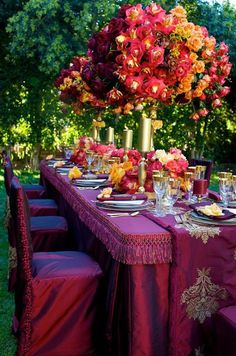 A visually stunning table setting that would suit a purple, red or gold/orange  themed event.