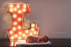 newborn with large retro light bulb background