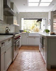 Rustic cottage kitchen features four skylights situated over an island topped with white marble lined atop a terracotta hex tile floor. Let's use a terracota hex tile floor instead of a quarry tile floor. Grey Kitchens, Home Kitchens, Rustic Kitchen, New Kitchen, Kitchen Redo, Design Kitchen, Kitchen White, Vintage Kitchen, Cheap Kitchen