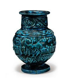 AN EGYPTIAN TURQUOISE GLAZED JAR   ROMAN PERIOD, CIRCA 1ST-2ND CENTURY A.D.   With spherical body, disc foot, short cylindrical neck and flattened rim, decorated in moulded relief with a main frieze of three ibex and prowling lion amongst berried foliate decoration, band of stylized lotus below, scrolling tendrils on the shoulder, neck with band of scrolling volutes and tendrils  7 in. (17.8 cm.) high