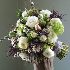 bouquet with bright green viburnum, white hyacinth, peach Menton French tulips, green parrot tulips, white ranunculus, French pussy willow, Snow Dance spray roses, euonymus foliage and deep purple agonis