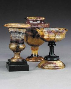 Three Blue John urns, century Comprising: a shallow bowl on black marble stems and dome foot -- high; an ovoid footed urn, with reeded banding -- high; and a campana urn, on waisted foot and black marble stepped base -- high Castleton Derbyshire, Tiffany Stone, Urn Vase, Popular Colors, Grand Tour, Decorative Accents, Black Marble, Rocks And Minerals, Rustic Furniture