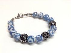 Bracelet en acier inoxydable # 591  VENDU Bracelet fait de agate tibétaine bleue/blanche et de billes d'acier inoxydable monté sur un fil et attache d'acier inoxydable. Grandeur 8 pouces (20 cm): -Agate tibétaine bleue/blanche de 10 mm -Billes d'acier inoxydable de 10 mm X 12 mm. Fait main