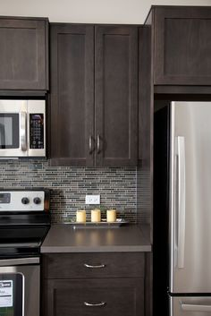 Brown maple shaker-style cabinets, stainless steel microwave, stove and fridge with glass mosaic tile backsplash at Prospect Rise Calgary townhomes by Avi Urban.