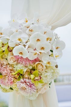 A mix of flowers, including orchids, roses and hydrangeas, decorated the altar curtains.