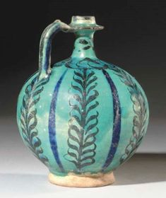 KASHAN TURQUOISE AND BLACK POTTERY BOTTLE  CENTRAL IRAN, CIRCA 1200  With spherical body on short unglazed foot rising to straight neck with wide collar and angular handle, the turquoise body painted under the glaze with vertical black leafy vines alternating with splashes of cobalt-blue, a register around the neck with a pattern of swirling fish, slight iridescence 7in. (17.8cm.) high