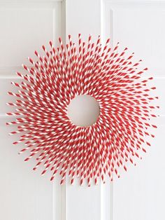 "Straw-Burst: It may just be red and white, but this wreath pops like no other—and it couldn't be more affordable, since it's crafted out of plain paper straws. Materials  • Pencil  • 6"" flat floral and craft ring (99¢; Michaels.com for stores)   • 1 sheet of white paper   • Scissors  • Hot-glue gun and glue sticks  • 1 box of 144-count paper straws   • Ribbon scrap  Step by step instructions"
