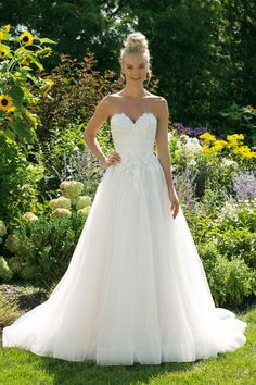 A ball gown fit for a princess. Sequined appliques adorn the sweetheart bodice and trickle into the top of the tulle skirt. Finished with horsehair at the hem, the full skirt is perfect for a night full of dancing.