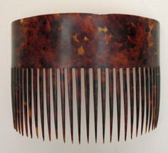 """1810s - 30s Large Dyed Horn Comb  This is most likely an American made comb in cow horn, dyed to resemble tortoiseshell. These were cut and hand sawn, often by itinerant comb makers. This comb is particularly well dyed - it really does look like tortoise. These were worn across the back of the head, often at an angle and were a simple accessory that complemented the simple Empire Styles.  Size: 9.5"""" Wide by 5"""" Tall"""